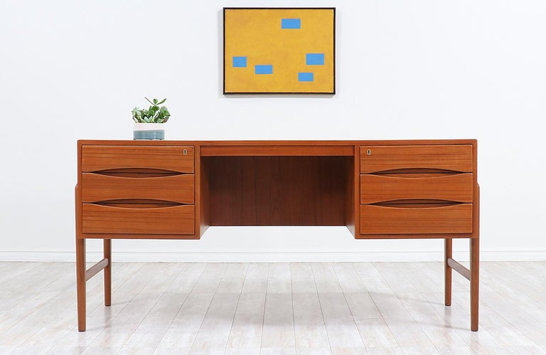 One of our most striking Danish Modern executive desks designed and made in Denmark in the 1950s. This Classic and elegant Danish desk features a solid teak frame with a stunning warm grain detail throughout and four sculpted legs that ascend from