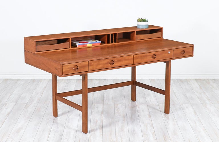 Spectacular teak desk designed and crafted by Peter Løvig Nielsen in Denmark, circa 1970s. Its ingenious design makes it versatile in accommodating two-persons on each side by simply flipping the top shelf and having the top removable drawers