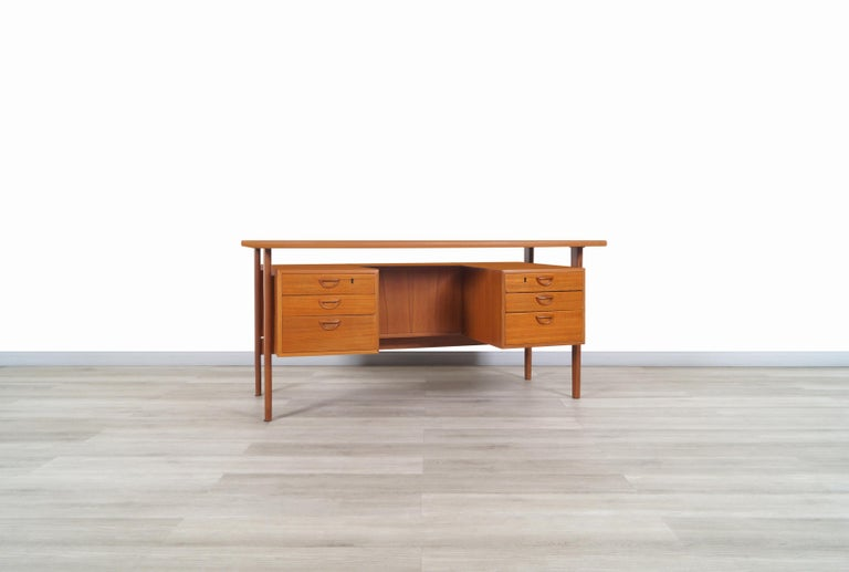 Amazing Danish modern floating top desk designed by Kai Kristiansen for Feldballes Møbelfrabrik in Denmark, circa 1960s. This desk is also known as model FM60. It represents one of the most coveted Scandinavian designs of the time. It's made of teak