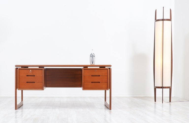 Stylish modern executive desk designed and manufactured in Denmark by Dyrlund, circa 1960s. This striking Danish modern design features a teak wood frame with three spacious drawers on each side and an open back with two ample compartments for