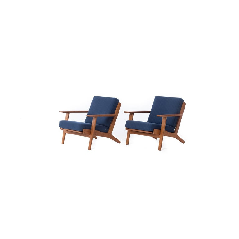An original set of GE290 lounge chairs by Hans J. Wegner for GETAMA. Original sprung cushions with blue pinstripe wool upholstery. 