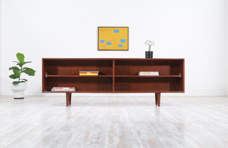 Stylish modern credenza or bookcase designed by H.P. Hansen in Denmark, circa 1960s. This skillfully crafted walnut credenza features a versatile shelved interior with three pins for quickly adjusting the interior in three different positions for
