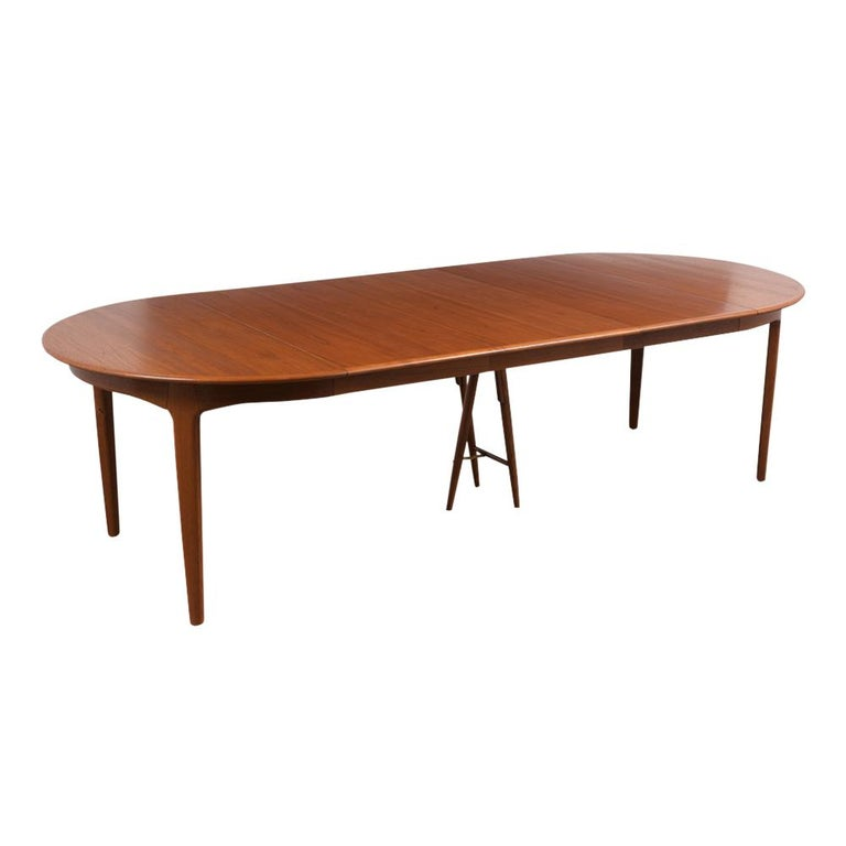 This Large Henning Kjaernulf for Soro Stolefabrik Danish Dining Table has been restored, made out of teak wood, and has its natural walnut stain finish. This Circular Top Table comes with three extra leaves that can be added/ removed with ease and