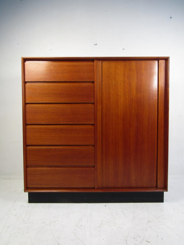 Stylish Danish midcentury high dresser. Teak wood exterior, with a black skirt base. Ample storage space between the dresser drawers on the left, and the sliding drawers on the right which are concealed by a well-made tambour door. A great piece