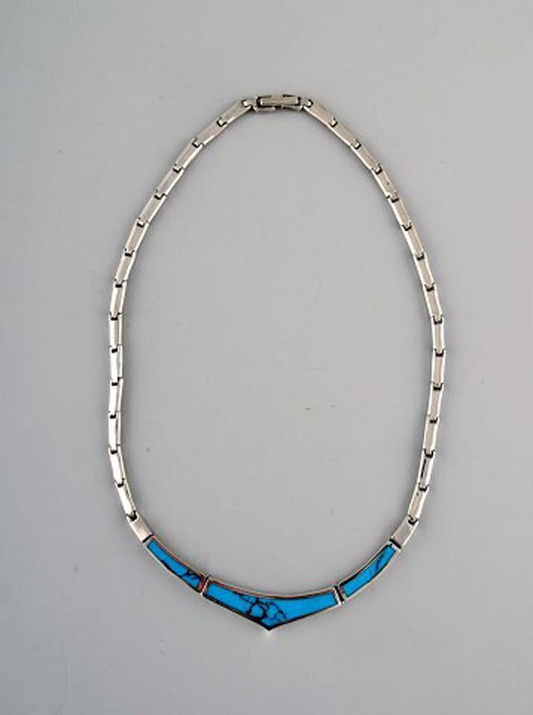 Danish modern jewelry set in sterling silver. 1960/70's. Comprising of necklace, ring and pendant with turquoise. In very good condition. Stamped. The ring measures: 20mm US size: 9,75. The pendant measures: 20 x 17 cm. Necklace total length: 41