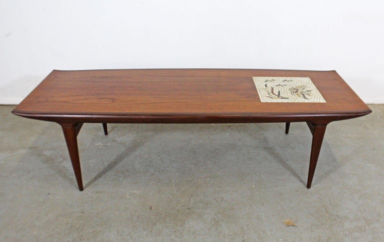 What a find! Offered is a vintage Danish modern teak coffee table with sculpted legs and top. Features a unique mosaic tile design on the tabletop with an underwater/Fish Design. It is in good condition with some age wear (see photos). It is signed