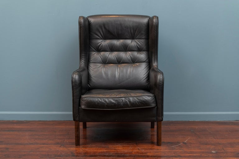 Danish modern black leather wingback chair, well made and well loved.