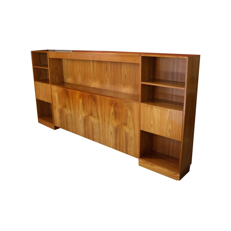 Gorgeous Scandinavian teak queen-size modular headboard with lighted bookshelf storage and nightstands, made in Denmark, circa 1970s. Features built in lighted center bookcase / shelf with two hidden reading lights on each side, eliminating the need