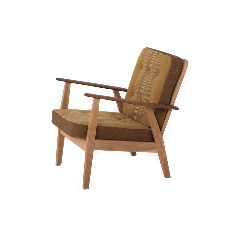 This Danish lounge chair in original vintage upholstery features sculptural teak arms atop a sturdy oak base.