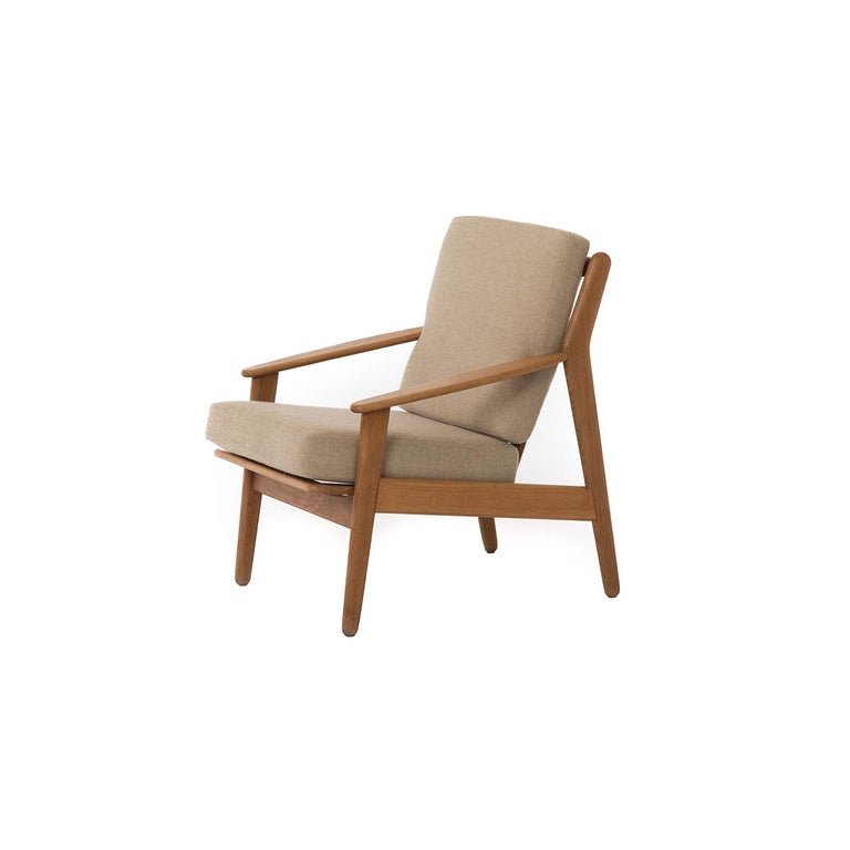 This vintage Danish Modern oak lounge chair has simple and Classic lines that could blend well into contemporary spaces. Cushions are a neutral pale-gold Hallingdal textile by Kvadrat in like-new condition.   Professional, skilled furniture