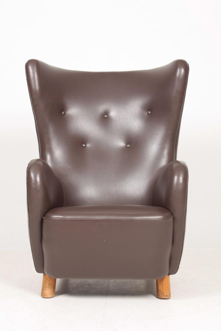 Lounge chair in upholstered in patinated saddle brown leather. Designed and made in Denmark, 1940s. Great condition.