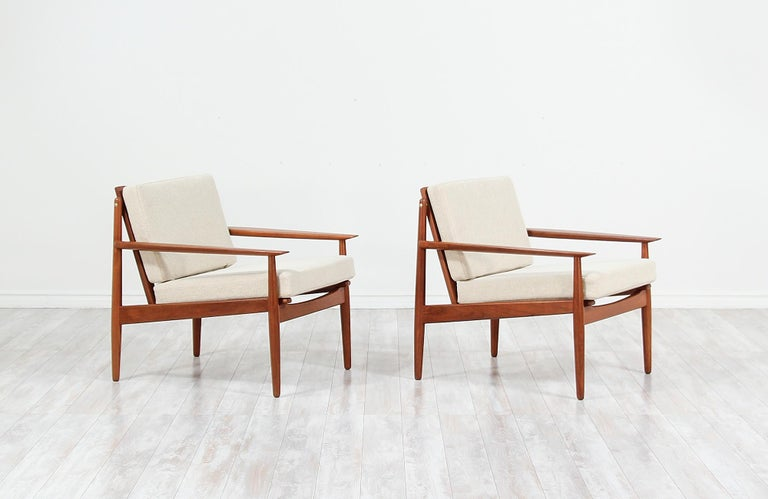 Pair of elegant modern lounge chairs designed by Svend Åge Eriksen and manufactured in Denmark by Glostrup Møbelfabrik, circa 1960s. This beautiful pair of lounge chairs feature a solid teak wood frame and sculpted armrests with organic shapes