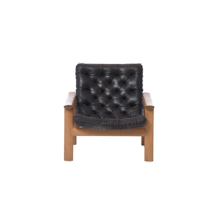 These low-profile oak lounge chairs feature dark brown tufted leather upholstery. Sold separately.