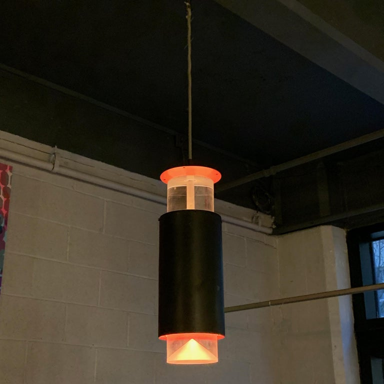 Danish modern, cylinder pendant light by Simon Henningsen plays with color and shadow to create a minimal, modernist feel. The light features suspended Lucite bands at top and bottom with black painted aluminum exterior band. The interior band and
