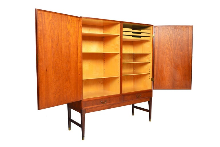 This Danish modern teak bureau offers a large storage capacity and sleek design. Two large locking doors open to reveal a beech- lined, two bay interior outfitted with six adjustable shelves and three drawers. Two lower drawers with original brass
