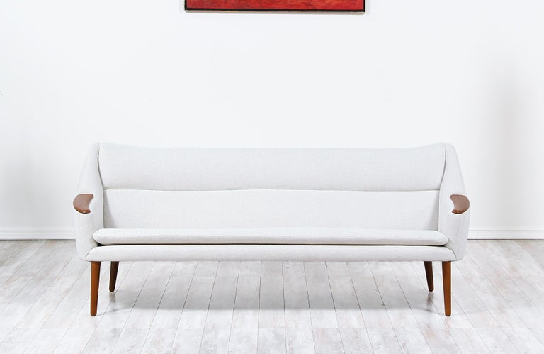 Beautiful vintage sofa designed by Kurt Ostervig for Rolschau Mobler in Denmark circa 1958. This rare design features a sturdy teak wood frame and armrests with a newly upholstered interior of high-quality foam and beige tweed fabric to add a clean