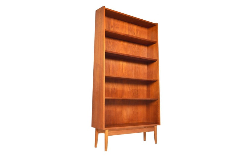 This stately Danish modern midcentury bookcase in teak by Nexø is the perfect storage piece for any modern home. Four adjustable shelves provide versatility for storage. Case stands on a beautiful teak base. In excellent original condition with