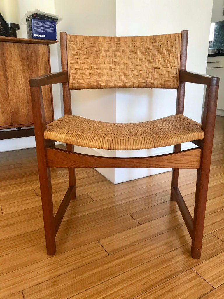 A handsome modernist design. Made of teak with rosewood armrest detail and caning. Great to use as an accent for occasional seating or add to a dining set...