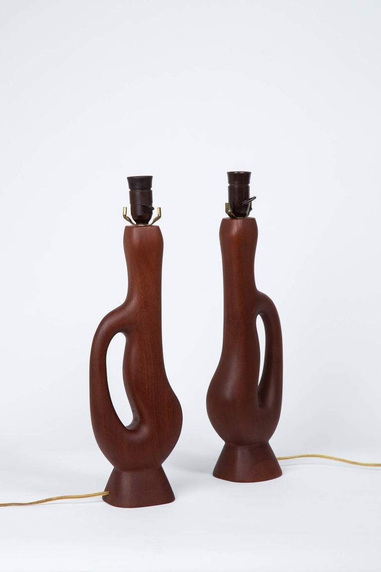 Pair of handcrafted organic form teak lamps with original woven lampshades. Bakelite sockets and light switches. Overall height 34.5
