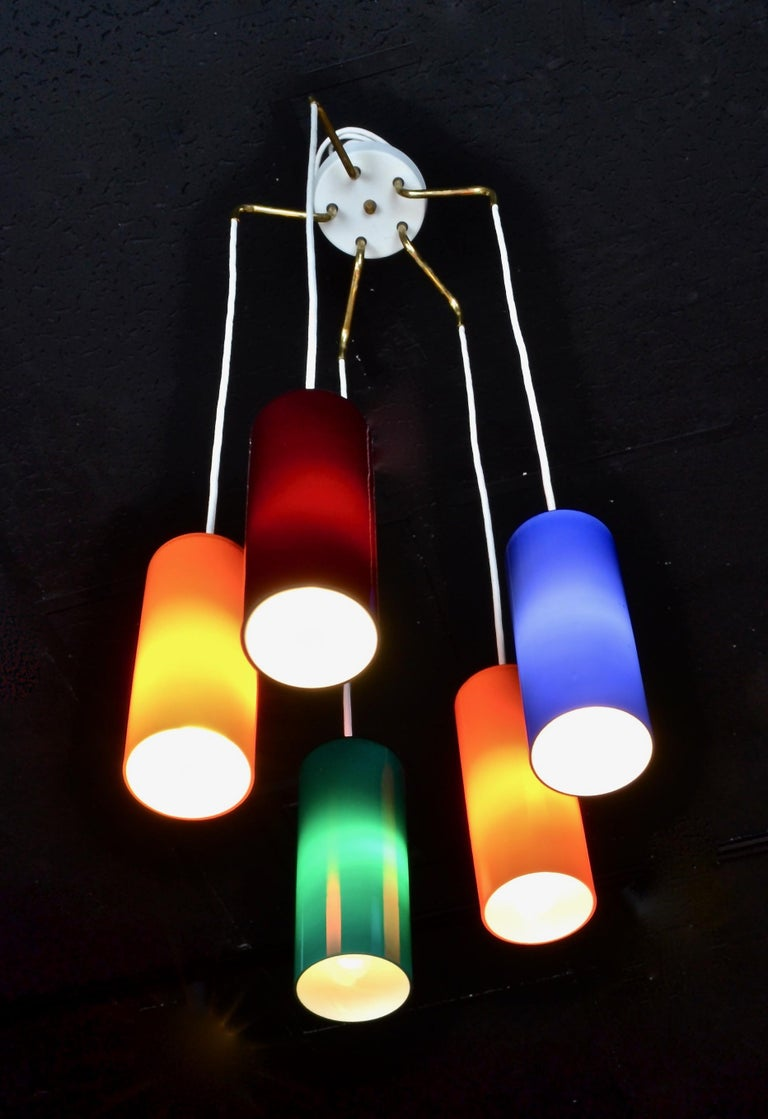 Five cylindrical vibrantly colored case glass pendants suspended from a center ceiling fixture. Shown at level lengths but extra wire provided so that pendants may be staggered if desired. Also, total length is adjustable. All updated wiring. Each