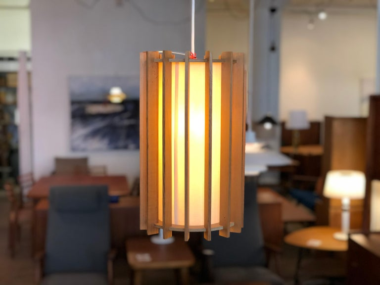 This conical piece boasts a fir slat exoskeleton and a linen shade lining inside. When light is on the fixture has a soft diffuse glow, a great accent for any modernist contemporary setting.