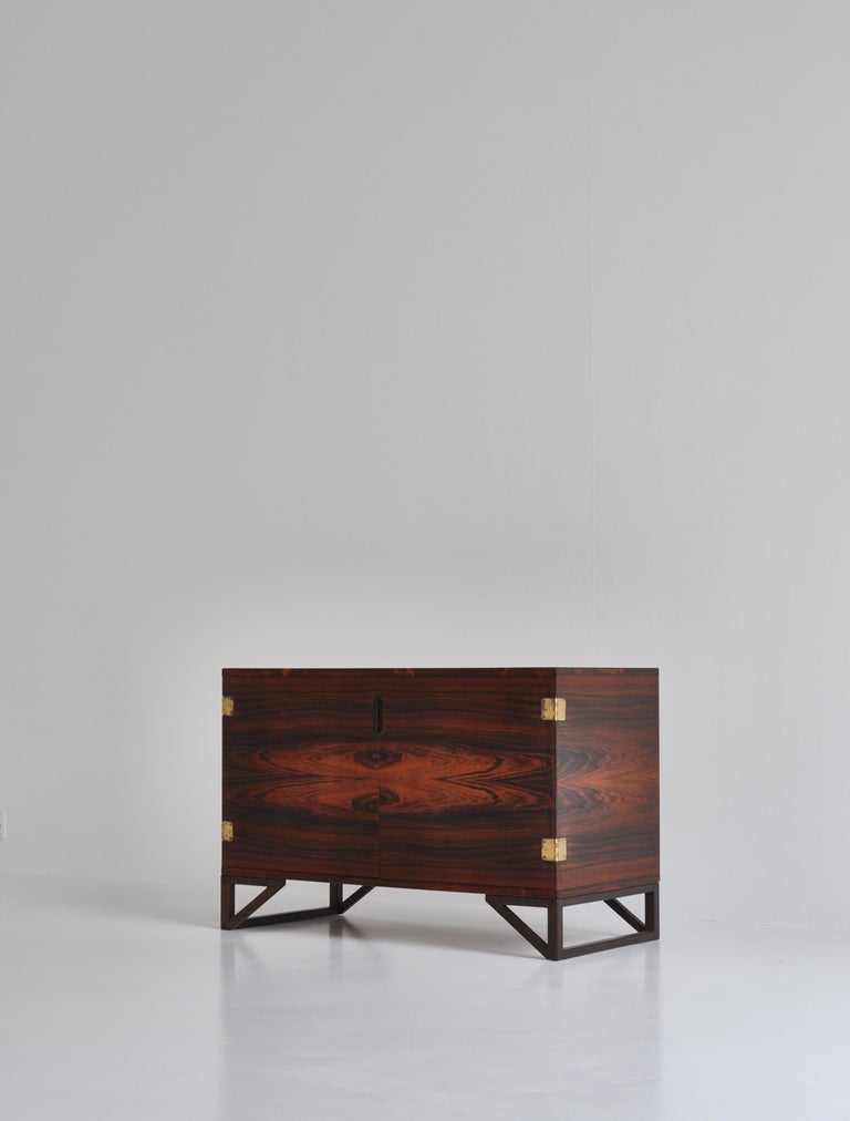 Elegant low sideboard in rosewood by Danish designer Svend Langkilde for Illums Bolighus in the 1960s. The elegant solid teakwood drawers features finger joints and can be pulled out and used as trays. The doors have beautiful hinges in patinated