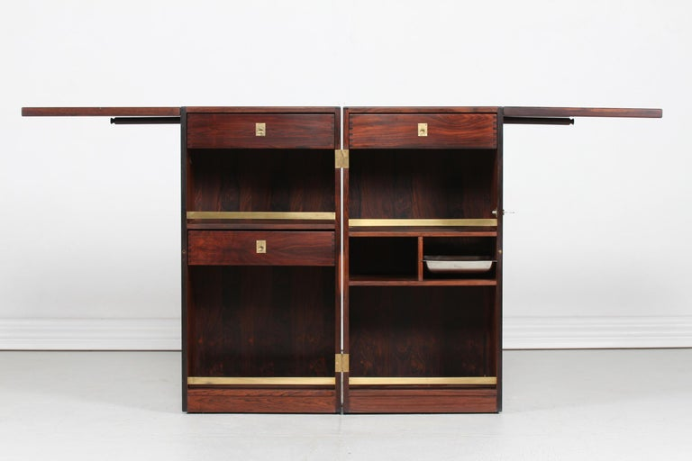 Here is the ultimate vintage captains bar by the Danish designer Reno Wahl Iversen. It's made of rosewood with brass fittings and top of dark green Formica by the Danish cabinetmaker Dyrlund. The bar can be closed and locked or be open for