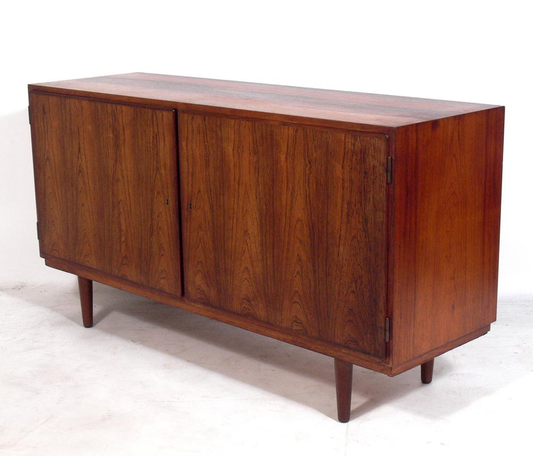 Danish modern rosewood credenza, designed by Poul Hundevad and retailed by Asbjorn Mobler, Denmark, circa 1960s. Beautiful graining to the rosewood. It offers a voluminous amount of storage with the left door opening to reveal three adjustable