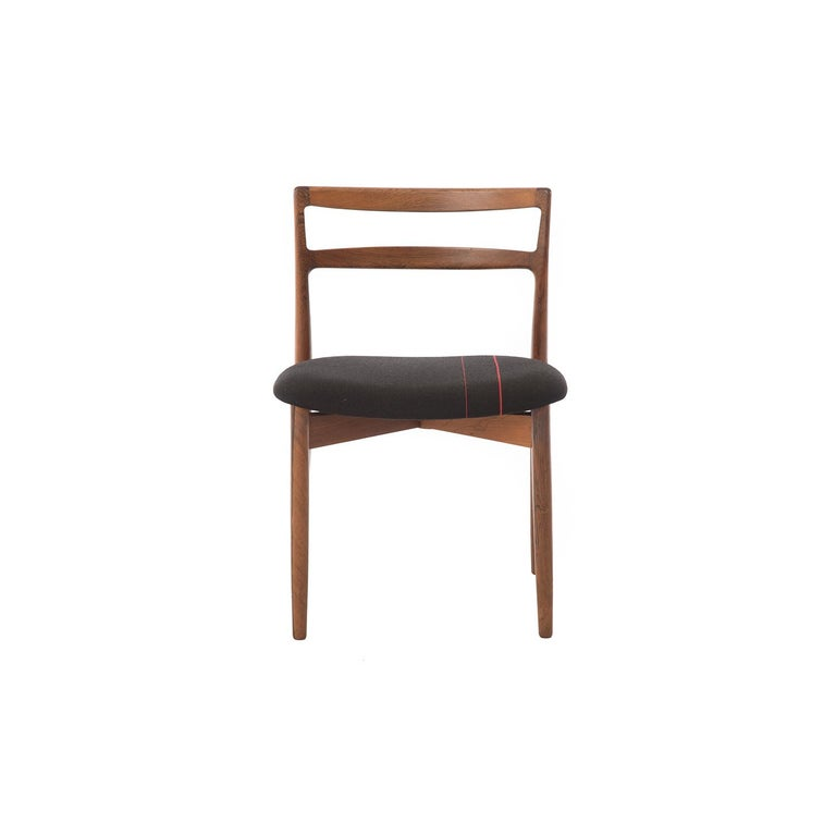 This set of 6 Harry Østergaard rosewood dining chairs feature a sleek ladder back design, which is offset by a wider and more plush seat, upholstered in mercerized wool, with slight racing stripes.