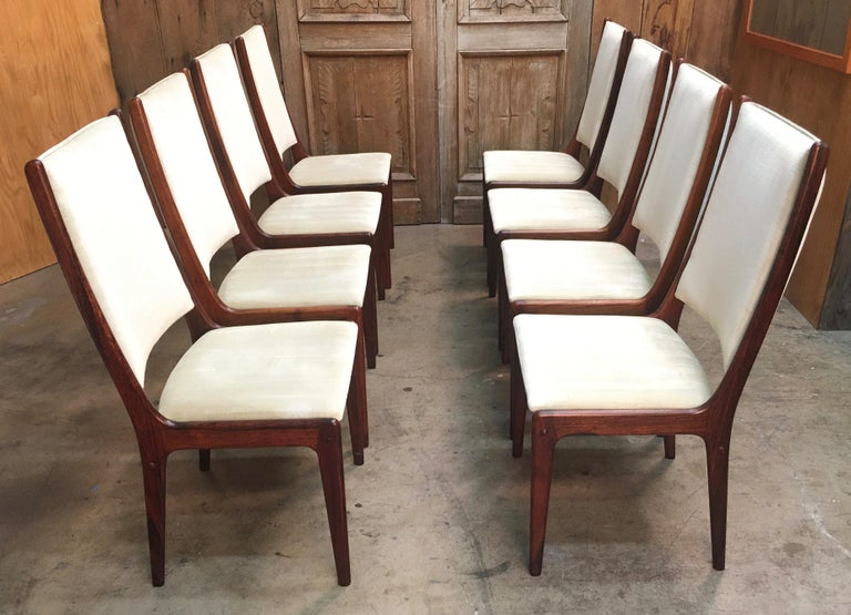Set of eight sculpted Danish modern rosewood high back dining chairs in the style of Johannes Andersen table not included.