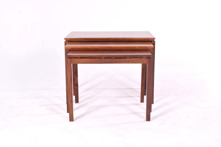 Set of three Danish rosewood nesting tables of ascending size. Fine construction, solid rosewood bolt-on legs and old growth, fiery, grain are just a few notable qualities. Seamless joinery and Classic Danish design gives these 1960s stacked tables