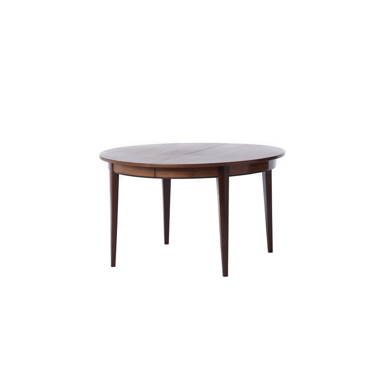 This beautiful and sturdy Danish modern original table is made from highly figured old growth rosewood which has an updated (new) lacquer finish for ease of use. This table comfortably seats four in its smallest iteration, 6 with one leaf and 8 (or