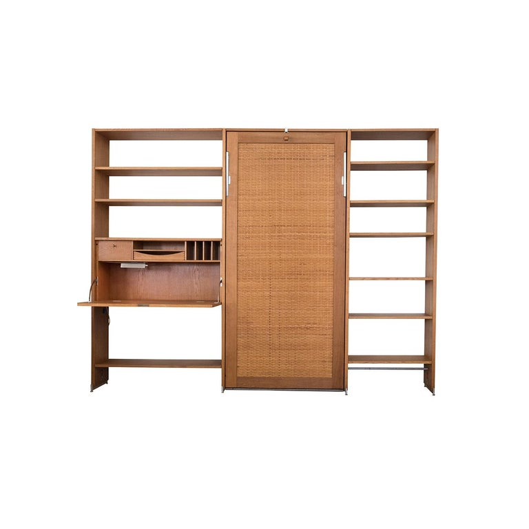 Danish Modern RY100 Murphy bed secretary and shelving system by Hans J Wegner for Ry. This Classic Murphy bed boasts a lovely cane front with heavyweight steel hardware and drop down bed upholstered in original Danish wool (we'll replace the wool in