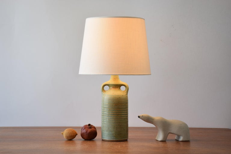 Stylish mid-century Danish table lamp from the ceramic workshop Knabstrup. Designed and made ca 1960s or 1970s. The lampbase is made of stoneware and has a matte pale green glaze with ochre golden elements. It has a structured striped