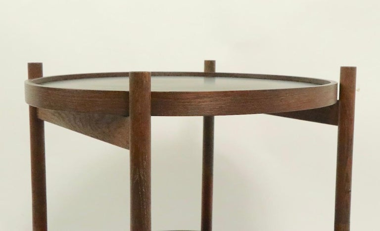 Rare Danish modern serving cart having two disk form removable trays, each with a red surface, and a black surface. The frame is solid teak, and folds to flat for easy moving and storage. The trays have laminate surfaces, each tray shows some