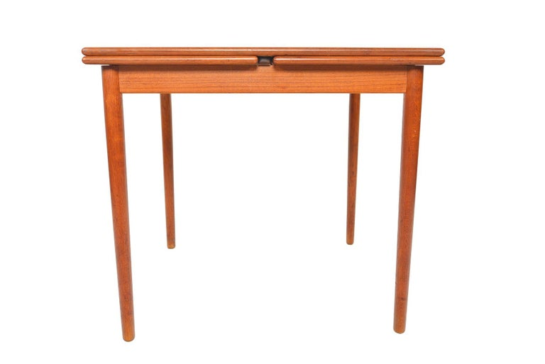 This fantastic Danish modern square draw leaf dining table is crafted in teak. Perfect for apartment living, this dining table offers a small footprint. When the two leaves are extended, the table nearly doubles in size. Great for entertaining! In