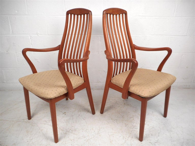 Stylish set of 6 Danish modern style dining chairs. Two of the six chairs have interestingly sculpted armrests. Contoured backrests with vertical stretchers give these chairs a great look. Sure to make a great addition to any modern interior's