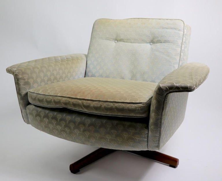 Very stylish Danish modern swivel chair and matching ottoman, with upholstered seat and back on teak star bases. Top quality design, materials, and construction, attributed to DUX, but unsigned. The upholstery is worn and will need to be replaced.