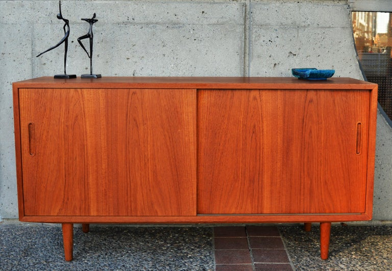 This hot Danish Modern teak compact buffet was designed by Hundevad & Co. in the 1960s and features gorgeous grain - check out those door fronts! - which open to reveal a beech interior with 3 adjustable shelves and one slim profile felted drawer. A