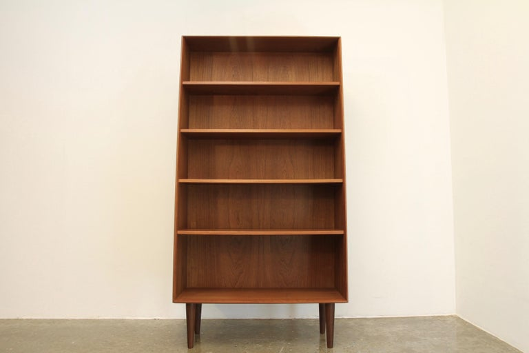 Very elegant Danish tall teak bookcase with slanting front and round tapered legs. This is fully original, and has been restored to a beautiful ready to use condition. A Classic retro design.