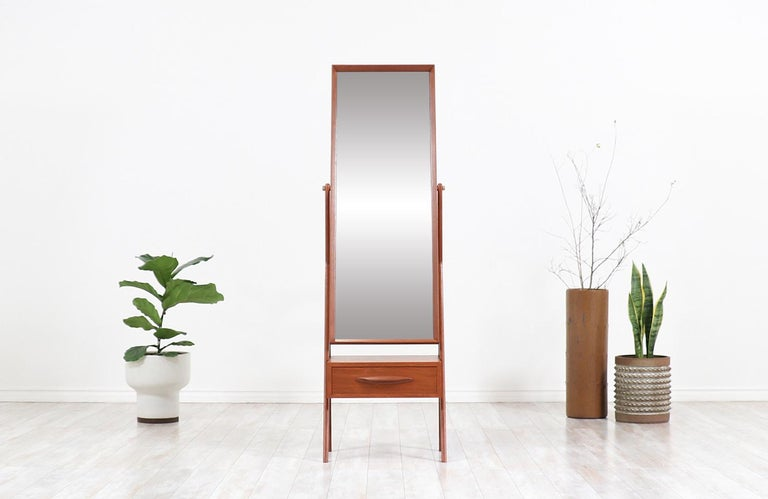 Classy Danish modern cheval dressing mirror designed and manufactured in Denmark, circa 1950s. This versatile dressing mirror features a solid teak construction with its original swivel mirror and an exquisite warm grain detail throughout the
