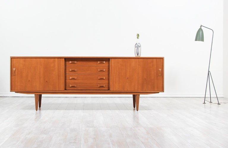 Mid-Century Modern credenza designed and manufactured by Clausen & Søn in Denmark, circa 1960s. This beautiful credenza features a sturdy teak construction over four tapered legs and a beautiful teak grain, adding a warm accent to this stylish