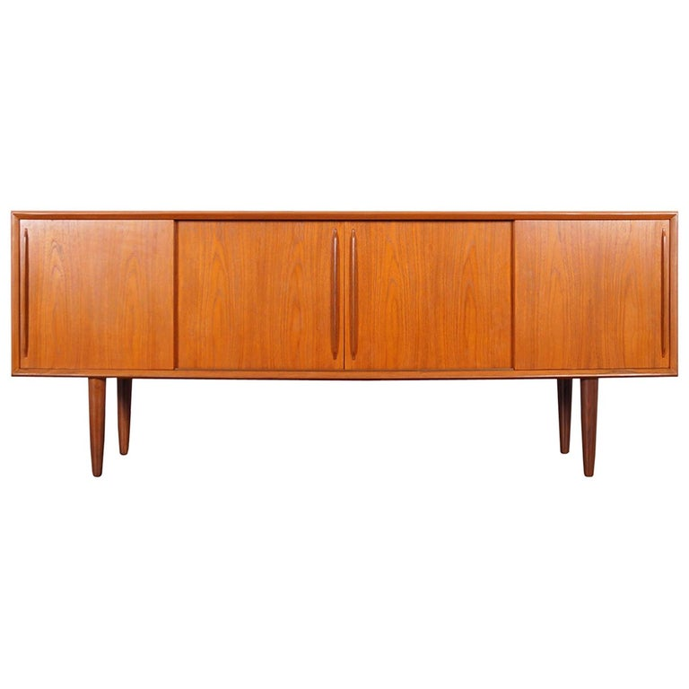 Amazing Danish modern teak credenza designed by Svend A. Larsen for H.P. Hansen in Denmark, circa 1960s. Features four sliding doors with sculptural pulls that open up to three sections. The middle section reveals a large adjustable shelf. On the