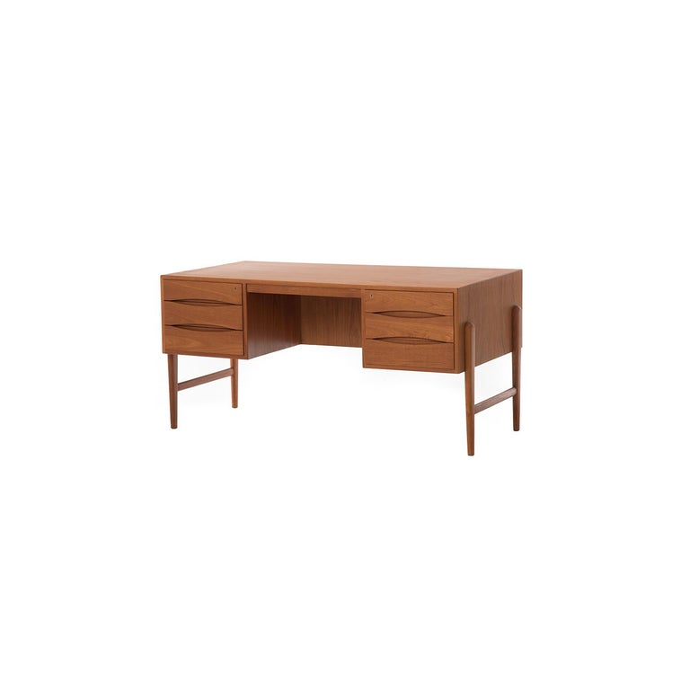 This large teak desk features six drawers (two locking) on the user side, as well as an open shelf/cubby space for additional storage on the backside.