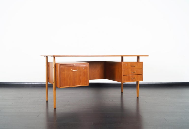 Amazing Danish modern teak desk designed by Torben Standgaard for Falster Møbelfabrik. This freestanding desk features a floating top design. Includes three drawers on the right side and a file drawer and pull-out writing surface on the left. On the
