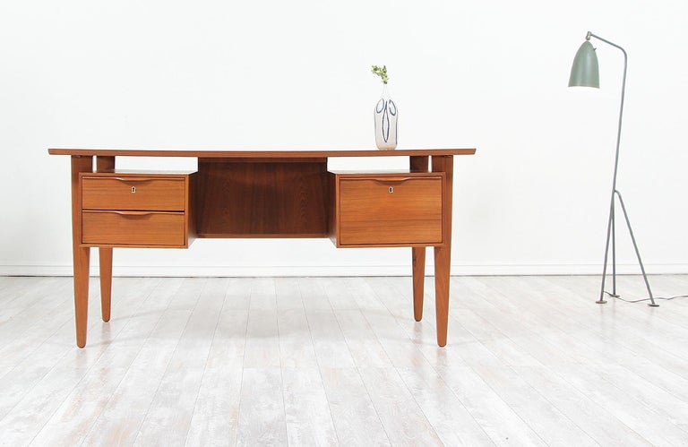 Elegant Danish modern desk designed and manufactured in Denmark, circa 1960s. This double-sided desk features a teak wood frame with three front drawers with sculpted handles and an open back with three compartments for optimal storage and many