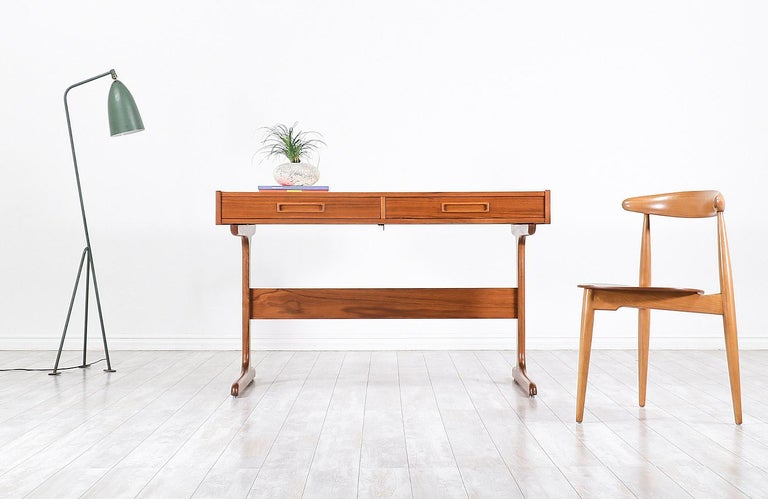 Versatile modern desk designed and manufactured in Denmark, circa 1960s. This stylish and sleek desk features a teak construction with two large full-size drawers and a sled leg design with a stretcher for added support. The top section hides a tray