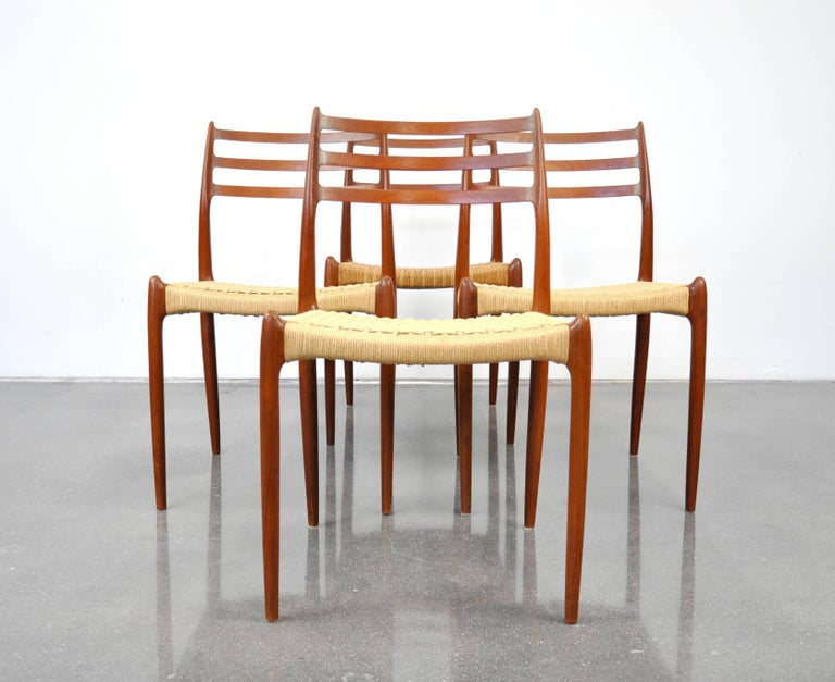 A vintage Mid-Century Modern teak dining set including a professionally restored draw-leaf extension dining table and a set of four model #78 chairs designed by Niels Otto Moller for J.L. Mollers Mobelfabrik in Denmark, dating from the 1960s. The