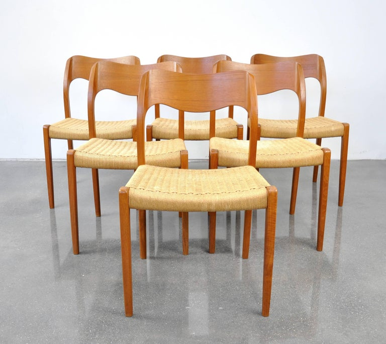 A vintage Mid-Century Modern teak dining set including a professionally restored draw-leaf extension dining table and a set of six model #71 chairs designed by Arne Hovmand-Olsen for J.L. Møllers Møbelfabrik in Denmark, dating from the 1960s. The