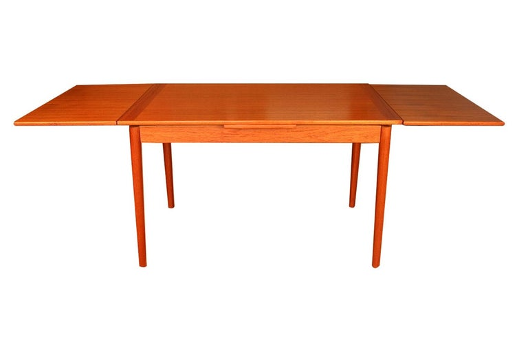 Beautiful, apartment sized midcentury Danish modern draw leaf extension teak table made in Denmark. With an initial small footprint, this table can also offer a generous space and double in size once its draw leaves are extended. Amazing design and